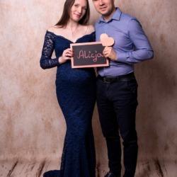 Rodzice trzymają tabliczkę z imieniem napisanym kredą - Alicja